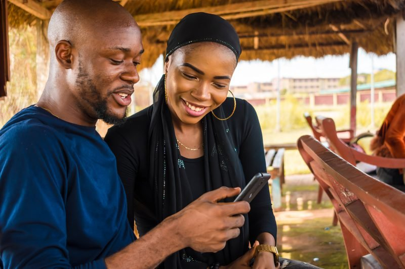 A smiling young couple in Africa use a mobile phone together.
